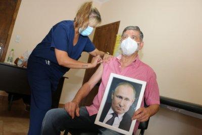 Кмет на аржентински град се ваксинира с портрет на Путин в ръце